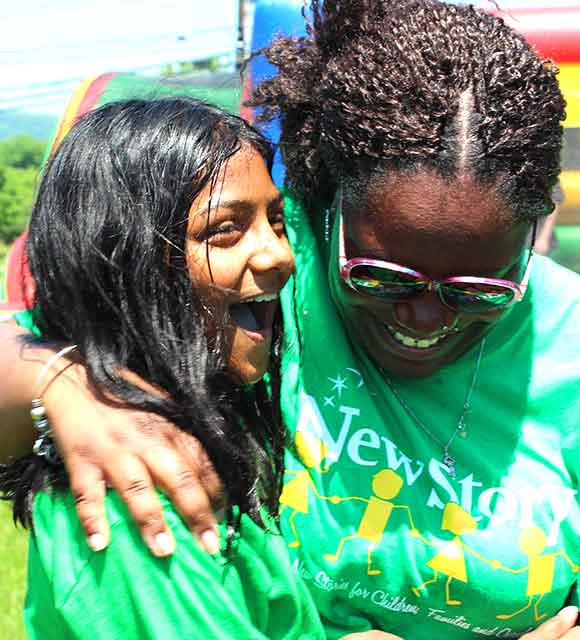 A student and support staff hug at their special needs school picnic.