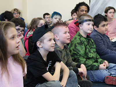 A group of young special education students sit together on the floor while listening to a presentation.