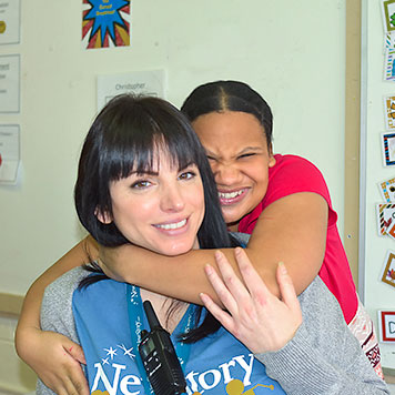 A students smiles and hugs her special education teacher in their classroom.