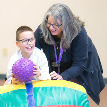 Staff member helping happy special education boy practice his balance by rolling on top of the rocking barrel to retrieve a ball in an occupational therapy session.