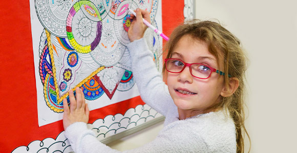 Elementary school special education girl coloring mandala poster on bulletin board.