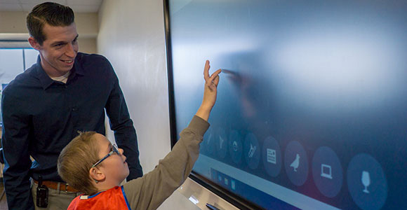 Elementary student in autism support program interacts with smart board in special education school