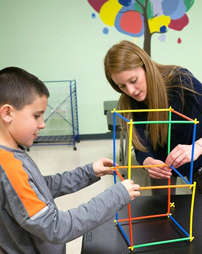 Special Education teacher and elementary student work together at a school to build a structure