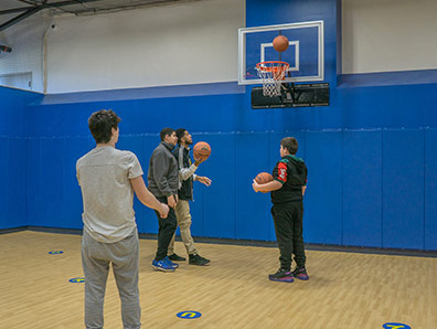 Four high school boys play basketball in the gym at a special education school.