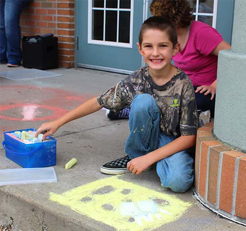 An elementary school boy smiles while drawing with chalk outside his special education school.