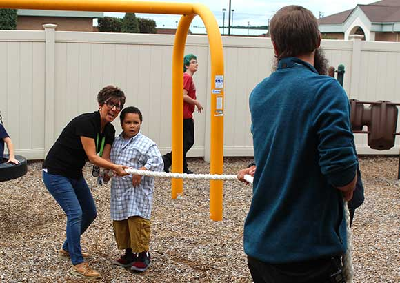 Special education teachers on a playground teach a young boy to play tug of war.