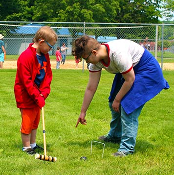 Two students at a special education school play croquet together during a picnic.
