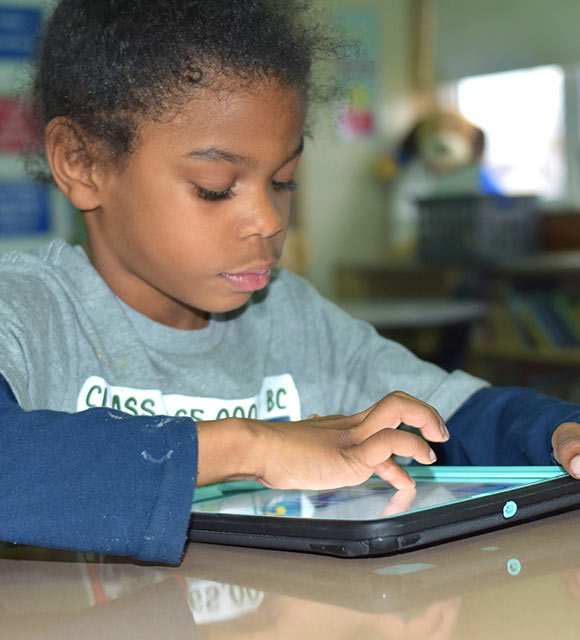 An elementary student works with an assistive device in her special education school.