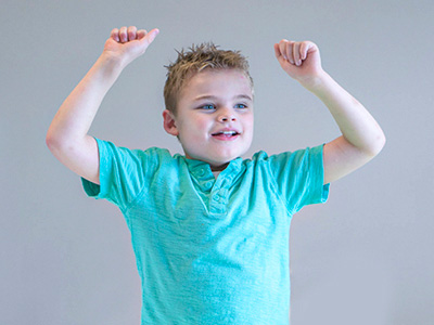 Elementary school special education boy with raised arms is happy to be at New Story Schools.