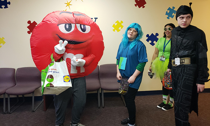 Students trick or treating in school. One dressed up in an inflatable red M&M costume, one in batman costume, one with blue hair.