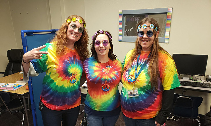 Three Teachers dressed up in very colorful hippie costumes: tie dyed shirts, glasses, beads and flower headbands.