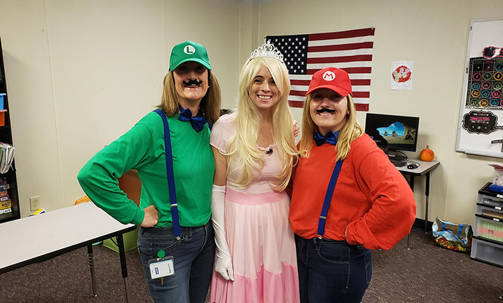 Three staff members dressed as The Mario Brothers, Mario and Luigi, and the center staff dressed as Princess Peach!