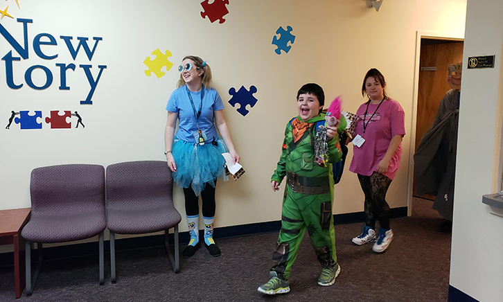 A child in a ninja turtles costume trick-or-treating in the hall. He looks excited, and maybe like he will attempt a ninja-turtle power high kick!