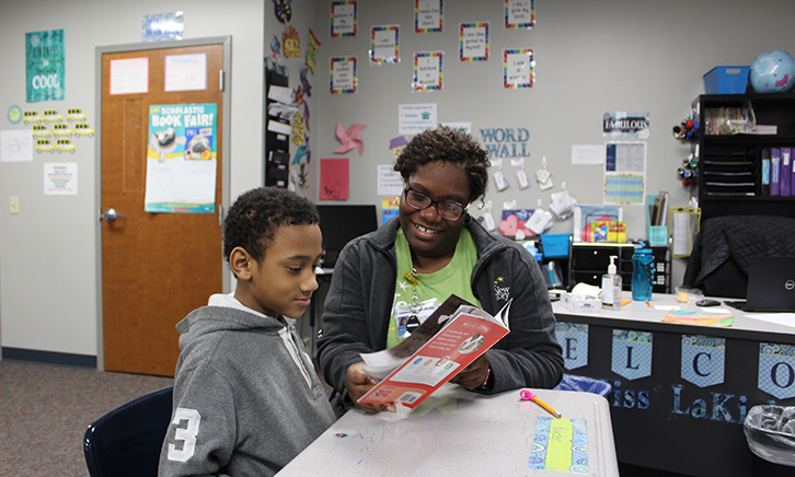 "Teacher works with young student. They read a book titled, ""Ruby Bridges"" together."
