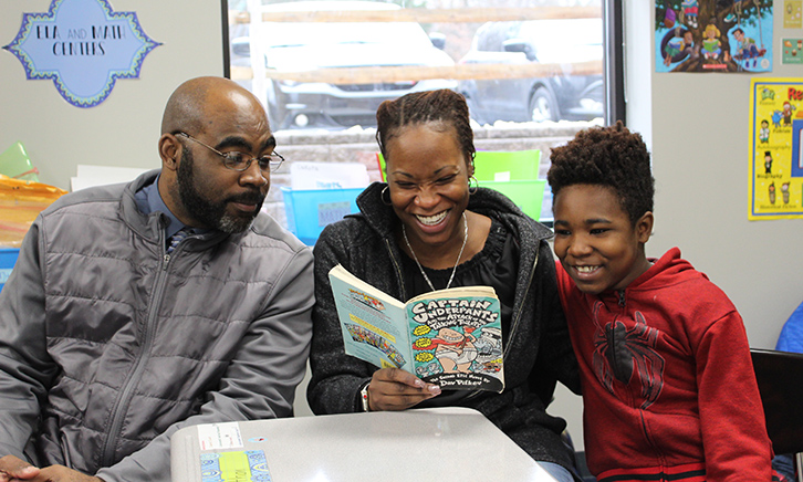"Mother and father read a grade level book called, ""Captain Underpants"" with their son. The mother is laughing."