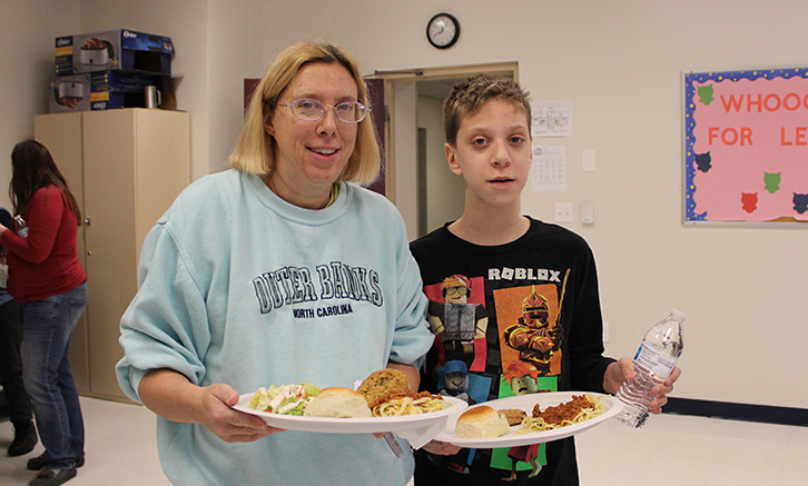 mother and son holding plates of spaghetti in the cafeteria