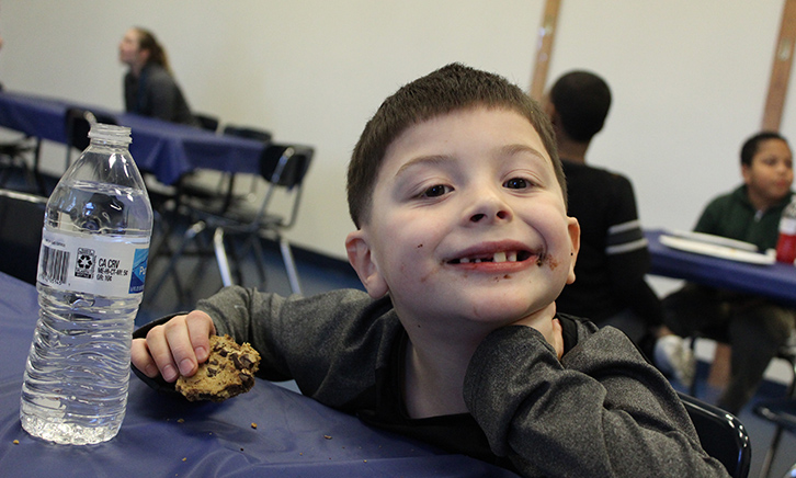 young student smiles a toothy grin as he eats a chocolate chip cookie. Melted Chocolate is smudged on his cheek.