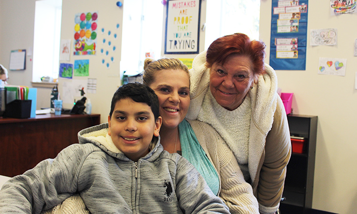Male Student, his Mother and Grandmother pose for a family photo in student's classroom.
