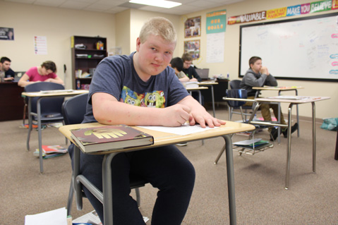 A special education high school student looks up from his desk while working on his lesson