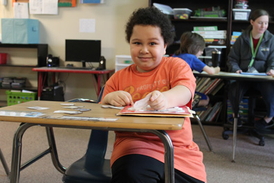A special education elementary school student looks up from his desk while working on his lesson