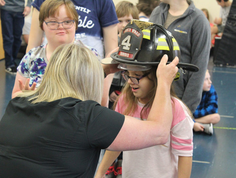 A young girl in an autism support program participates in a fire safety lesson