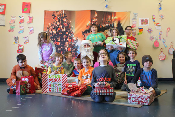 Students in an autism support program gather around Santa at their special needs school