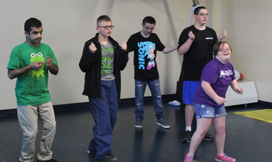 A class of high school special education students dances in the gym