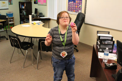 A high school student shows off a toy she is using in her special education classroom