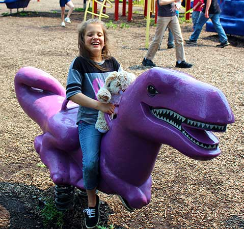 A young girl holds her stuffed animal while riding a purple dinosaur playground toy