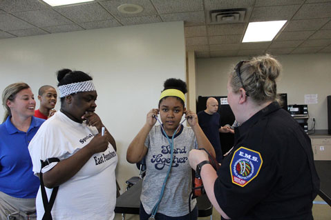Special needs students smile as they work with EMTs and try on stethoscopes