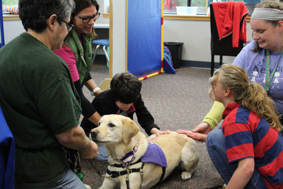 Special needs students pet a dog and smile as their teachers look on