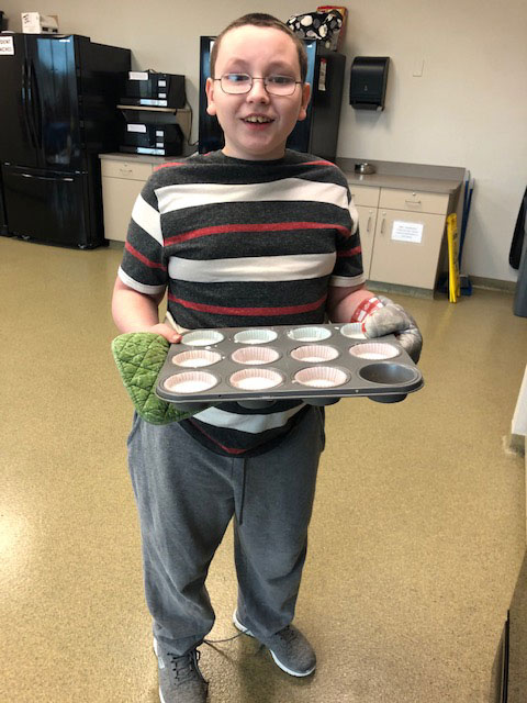 A special education student smiles for the camera and holds a tray of cupcakes