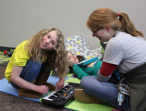 A special education teacher and two students play with a keyboard during their lesson