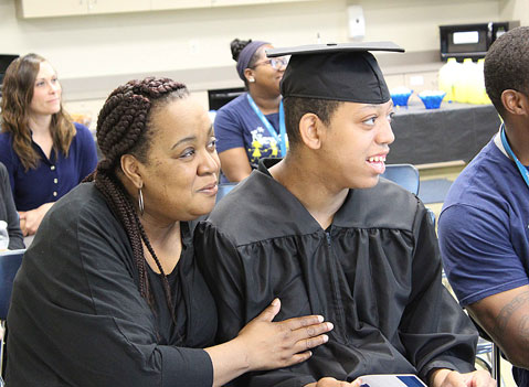 A mother smiles with her son in his cap and gown as he waits to graduate