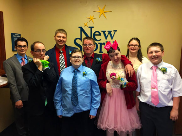 A group of high school studnets in formalware smile before prom at their special education school.