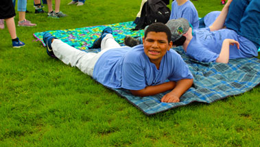 A high school student in a blue shirt smiles on a blanket.
