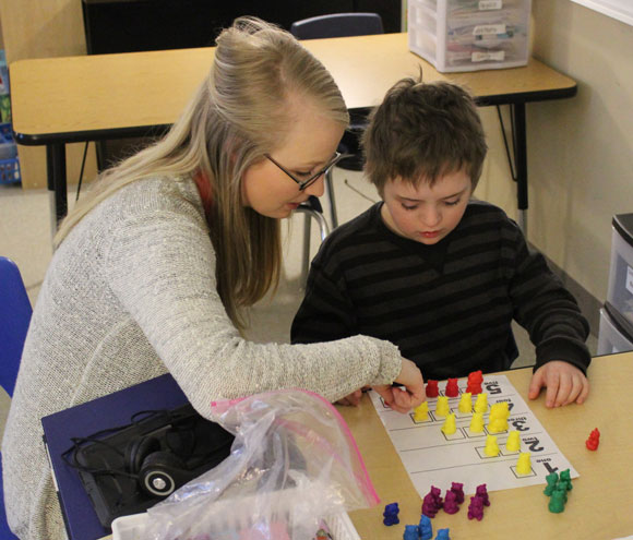A special education teacher works with her elementary school student on a project.