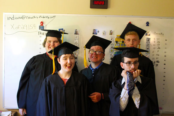 Five special needs students smile in their caps and gowns for graduation.