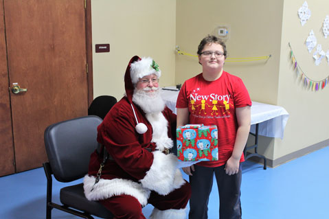 A special education student stands next to Santa Claus and smiles.