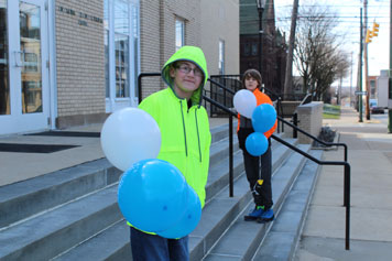 Two middle school boys hold baloons and smile on the steps of their special needs school.