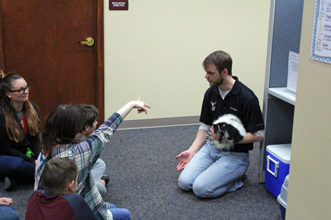 A man holds a black and white animal and talks to a group of special education students.
