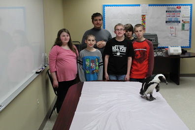 A group of special education students stand in front of a penguin and smile for the camera.