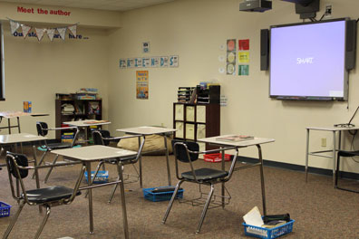 An autism support classroom with desks facing a smart board