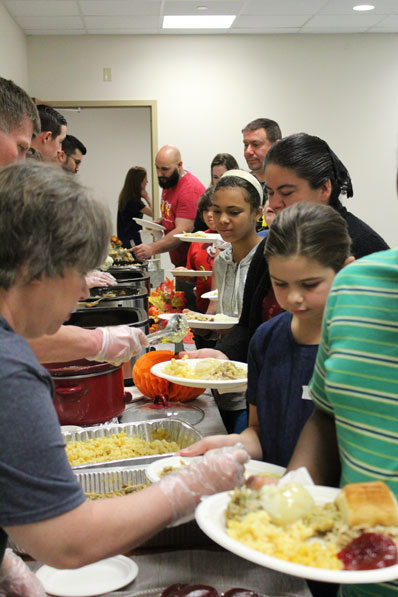 Parents, students, and faculty wait in line for a holiday buffet at their special education school.