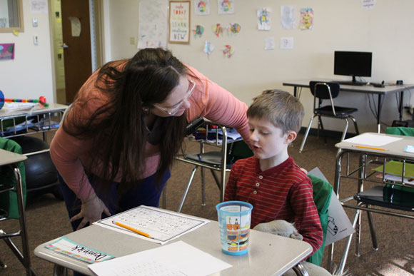 A special education teacher leans over an elementary school boy during class.