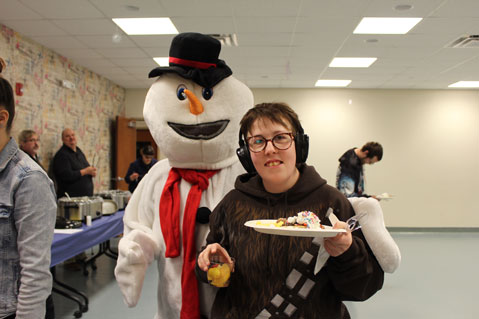 A man in a snowman costume stands behind a student at his special needs school.