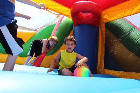 Two elementary school students smile in a bounce house at their special education school.