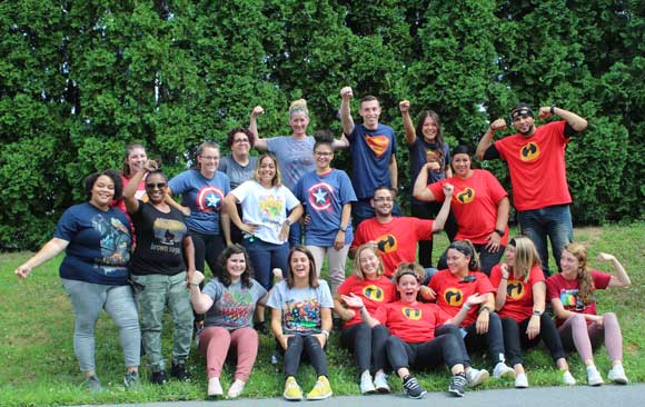 A group of special education teachers and staff smile in superhero shirts