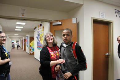 A boy and his special education teacher smile from the hallway.