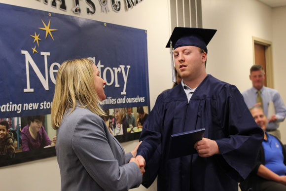 A high school student smiles at the camera during his special education graduation.